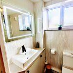 Ensuite bathroom with LED anti-fog vanity mirror and designer tap.